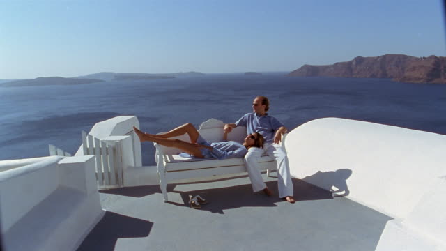 Wide shot couple lounging on bench on terrace with view of Aegean Sea / Santorini, Greece