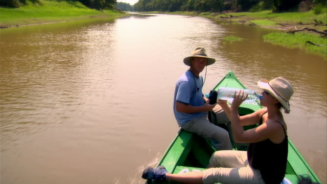 wide shot couple on small boat going up river/ the amazon, brazil - paar mittleren alters stock-videos und b-roll-filmmaterial