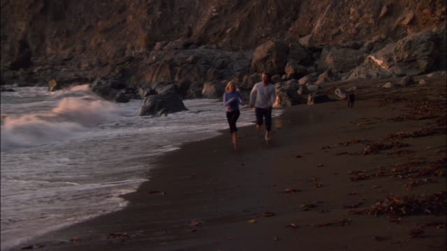 wide shot couple running on beach at sunset as tide comes in/ monterey county, california - ragged point stock videos and b-roll footage
