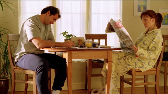 Wide shot couple sitting at kitchen table with woman reading newspaper and man looking frustrated