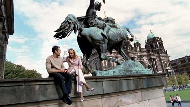 Wide shot couple sitting near statue looking at digital camera near Altes Museum w/Berlin Cathedral in background
