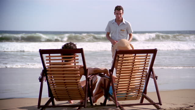 wide shot couple sitting on deck chairs on beach with surf in background / woman asking waiter to take photo - beach chairs stock videos & royalty-free footage
