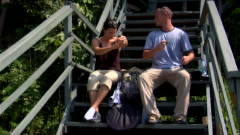 wide shot couple sitting on steps, applying sunscreen and drinking water/ the amazon, brazil - 虫除け点の映像素材/bロール