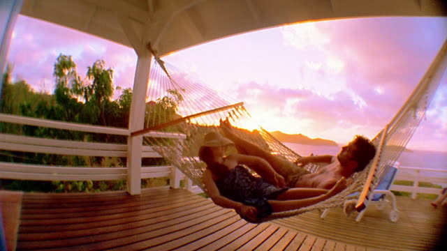 Wide shot couple swinging and resting in hammock with ocean in background at sunset / St. Barts, Caribbean