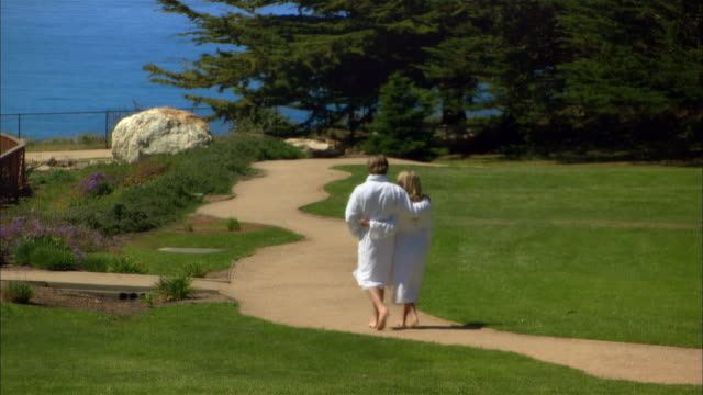 wide shot couple walking down path near sea/ monterey county, california, usa - ragged point stock videos and b-roll footage