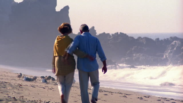 Wide shot couple walking on beach away from camera with seagulls and rock formations in background / California