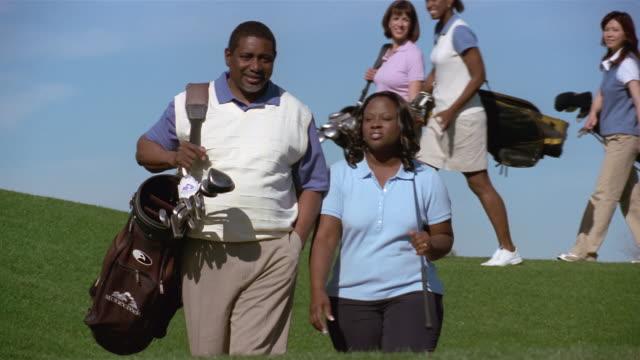 vídeos de stock, filmes e b-roll de wide shot couple walking on golf course carrying golf clubs / women golfers walking past in background - bolsa de golfe