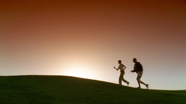 wide shot couple walking over hill at sunrise - racewalking stock videos and b-roll footage