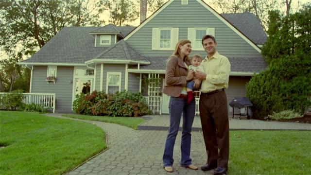 wide shot couple with baby standing in front of suburban house/ solebury, pennsylvania - paar mittleren alters stock-videos und b-roll-filmmaterial