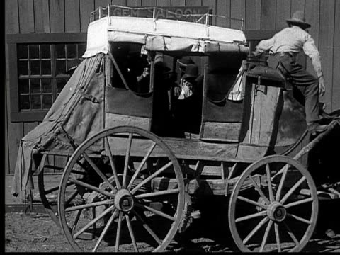 1915 b/w wide shot cowboy parking stagecoach in front of saloon  - 1915年点の映像素材/bロール