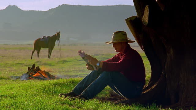 wide shot cowboy reading newspaper / campfire and horse in background - 20 24歳点の映像素材/bロール