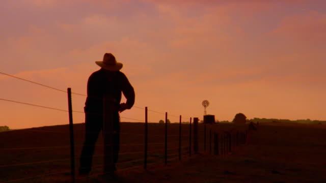 vídeos de stock, filmes e b-roll de wide shot cowboy repairing fence at sunset - ranch