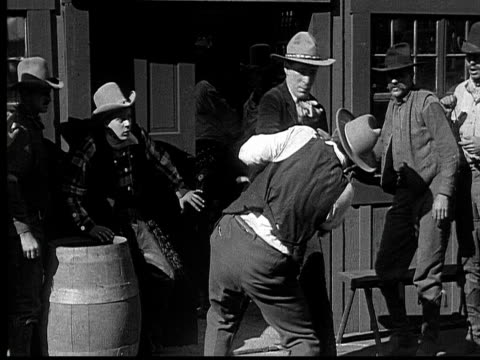 1915 B/W Wide shot Cowboys fighting outside saloon while other cowboys watch