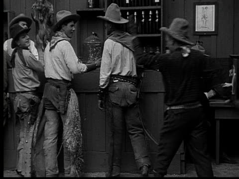 vidéos et rushes de 1915 b/w wide shot cowboys talking and drinking in saloon  - ouest américain