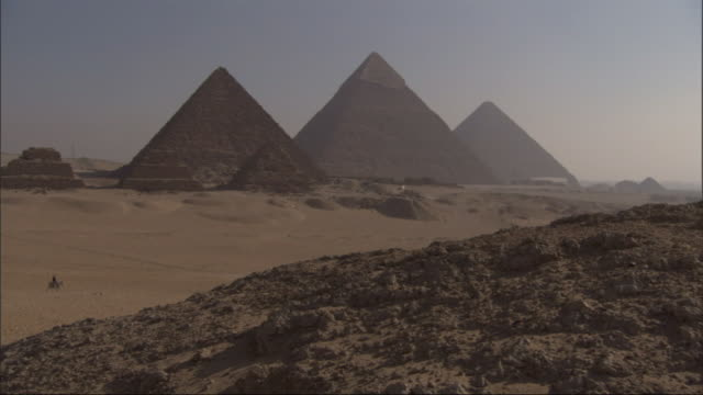 wide shot, crane - nomads ride camels near the great pyramids in egypt - pyramide bauwerk stock-videos und b-roll-filmmaterial