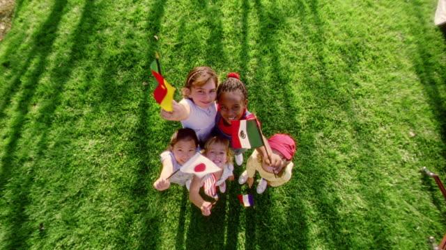 OVERHEAD wide shot crane shot away from + toward 5 girls smiling to camera waving small various international flags