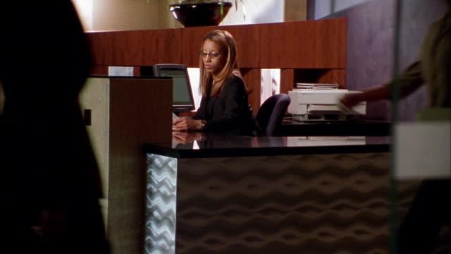 vídeos de stock, filmes e b-roll de wide shot crane shot black receptionist taking document from businessman in busy office - secretária
