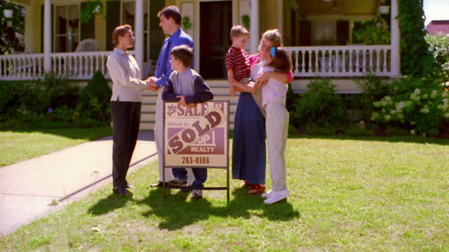 wide shot crane shot family standing with real estate agent in front of house with 'sold' sign - estate agent sign stock videos & royalty-free footage