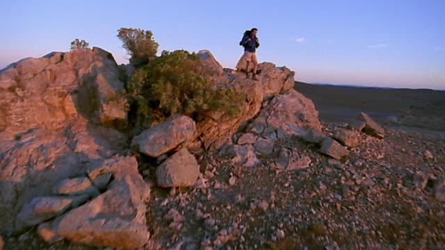 wide shot crane shot hiker standing on rock formation in desert - crane shot stock videos & royalty-free footage