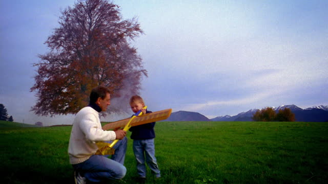 wide shot crane shot man and boy holding large toy glider on hillside meadow with tree + mountains in background / germany - crane shot stock videos and b-roll footage