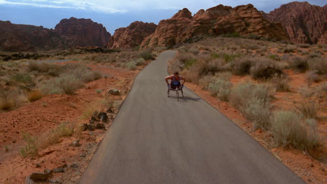 wide shot crane shot man in racing wheelchair on road in red rock canyon - paraplegic stock videos & royalty-free footage