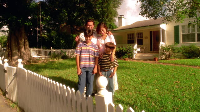 wide shot crane shot portrait family posing in front yard of house with man raising rabbit ears over older boy - picket fence stock videos and b-roll footage