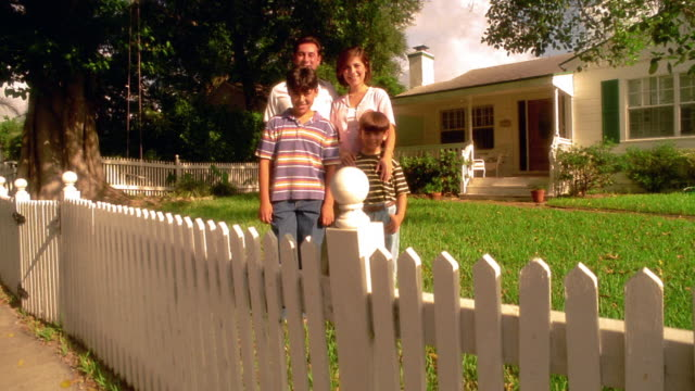 wide shot crane shot portrait hispanic family posing in front yard of house with picket fence in foreground / florida - picket fence stock videos & royalty-free footage