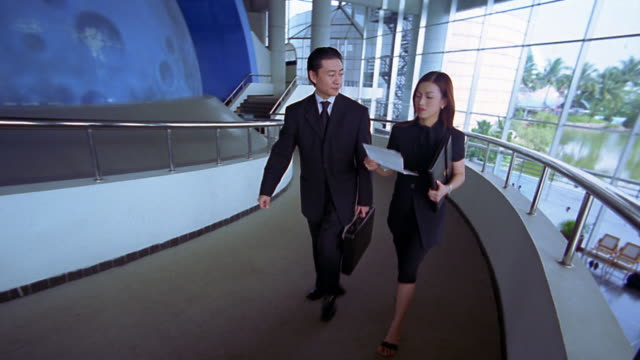 Wide shot crane shot tracking shot Chinese businessman and businesswoman on walkway in office building