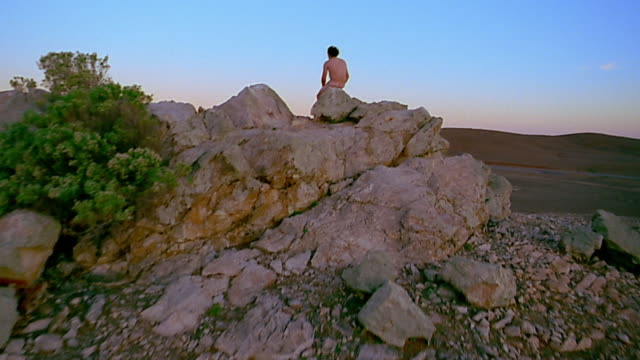 vidéos et rushes de wide shot crane shot up to naked man on rock ledge - 20 24 ans
