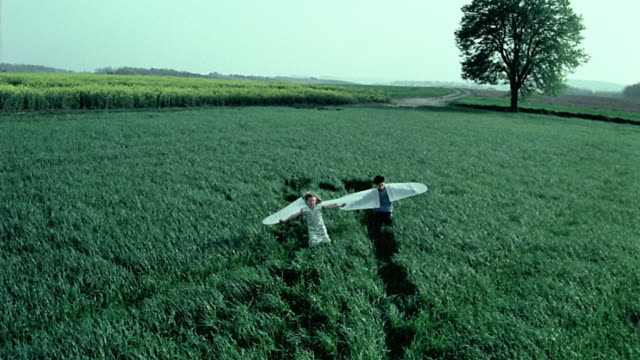 wide shot crane shot young girl and boy running in field with paper wings attached to their arms / belgium - costume stock videos & royalty-free footage