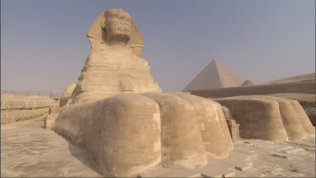 wide shot, crane - the sphinx stands majestically in the desert / egypt - male likeness stock videos & royalty-free footage