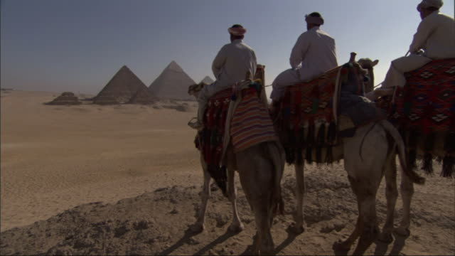 Wide Shot, crane - Three men on camels stand on a hill near the Great Pyramids in Egypt