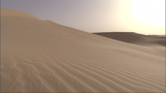 wide shot, crane tracking-left - the sharp peak of a golden sand-dune stands out against a fiercely yellow sun / egypt - sandig stock-videos und b-roll-filmmaterial
