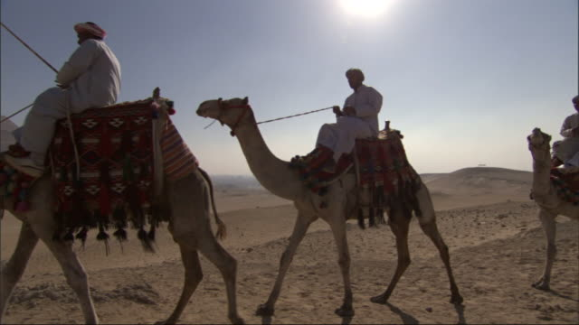 Wide Shot, crane tracking-left - Three men ride camels near the Great Pyramids in Egypt