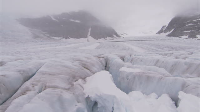 """wide shot crane tracking-left-fog settles over crevasses on the juneau ice fields. / alaska, usa"" - crane shot stock videos & royalty-free footage"