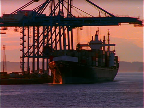 wide shot crane unloading containers from freighter at port at sunset/rise / Tacoma, Washington
