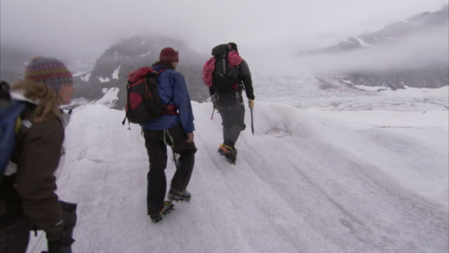 """wide shot crane-hikers trek across the juneau ice fields. / juneau ice fields, alaska, usa"" - crane shot stock videos & royalty-free footage"