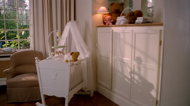 vídeos y material grabado en eventos de stock de wide shot crib and teddy bears on shelf over cabinets in nursery - cuna