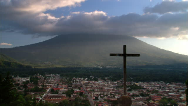 wide shot cross on hill with a village and a mountain in background / antigua, guatemala - guatemala stock videos & royalty-free footage