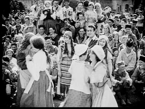 1916 b/w wide shot crowd gathered round peasants dancing in town square - 1916 stock videos & royalty-free footage