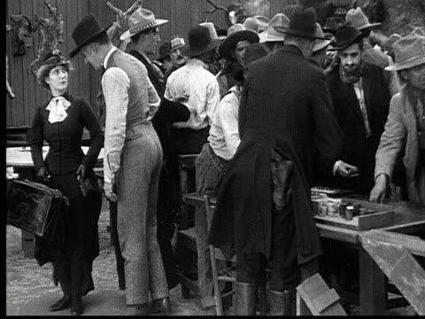 1915 b/w wide shot crowd of cowboys leaving gambling saloon  - 1915年点の映像素材/bロール