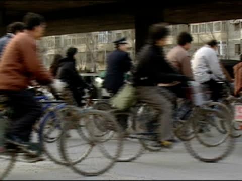 vídeos de stock, filmes e b-roll de wide shot crowd of cyclists riding with traffic under overpass/ beijing - passagem subterrânea via pública