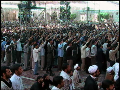 wide shot crowd of men protesting with fists in air / iran - iran stock videos & royalty-free footage
