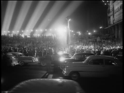 vídeos de stock, filmes e b-roll de b/w 1956 wide shot pan crowd traffic klieg light beams in front of grauman's for giant premiere / night - estreia