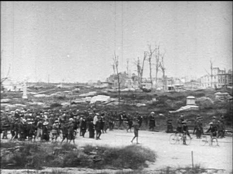b/w 1919 wide shot pan crowd walking past bombed buildings / belgium / documentary - 1919 stock-videos und b-roll-filmmaterial