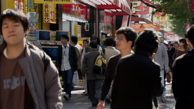 Wide shot crowd walking past electronics stores on sidewalk in Akihabara district / Tokyo