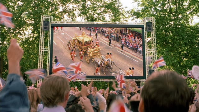 wide shot crowd waving union jack flags while watching carriage procession on large screen - large scale screen stock videos & royalty-free footage