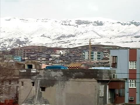 stockvideo's en b-roll-footage met wide shot crowded apartment buildings surrounding empty lot in rundown area of city/ silopi sirnak province turkey - torenspits