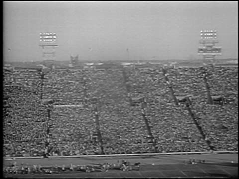 vídeos de stock e filmes b-roll de b/w 1965 wide shot crowded stadium in army vs navy football game / philadelphia / newsreel - cadete
