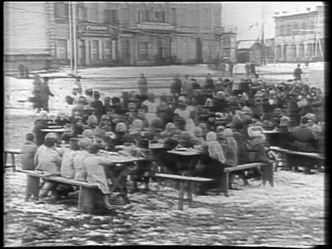 stockvideo's en b-roll-footage met b/w 1921 wide shot crowds eating at tables outdoors in winter / russia / newsreel - 1921